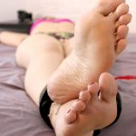 Anna endures tickles on the bed from head to toes