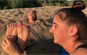 Veronika tickles Kristi's Revenge feet buried in sand public tickling!