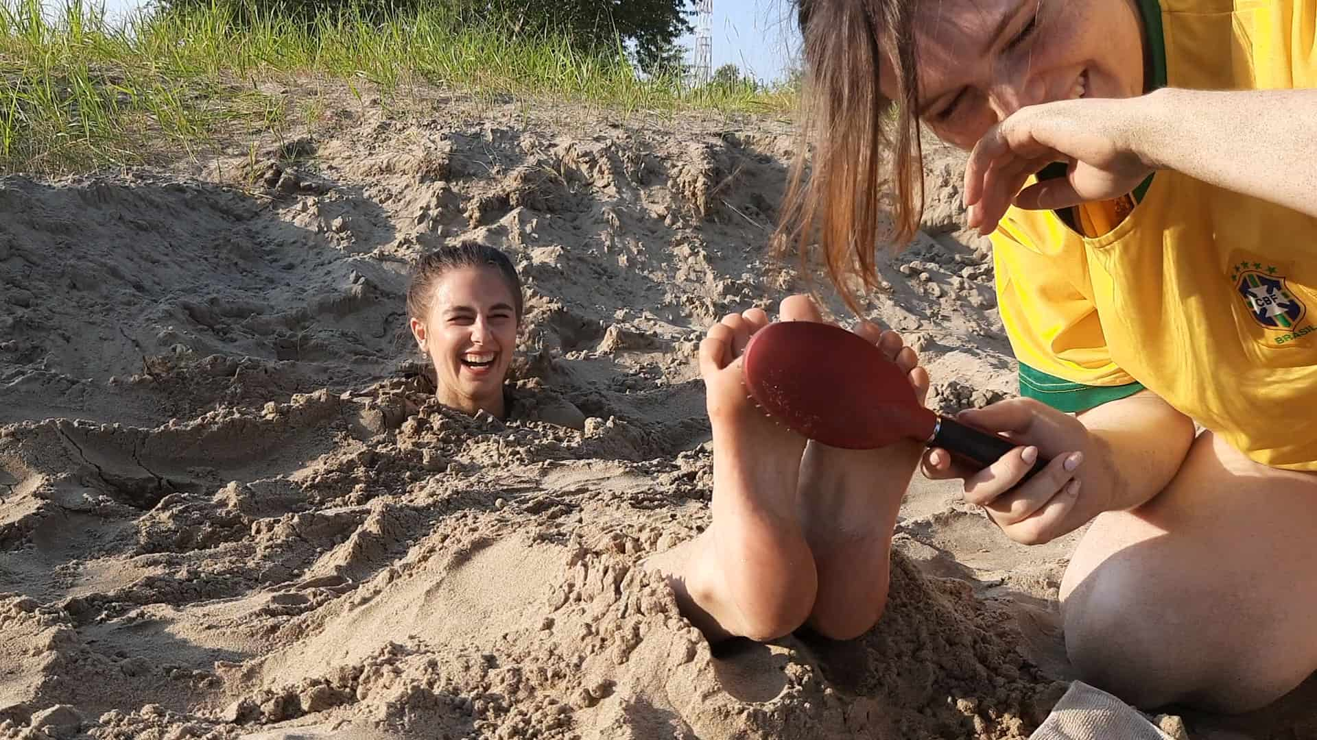 Karine gets revenge on Irina and tickles her feet while buried in public!